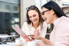 Жизнерадостные женщины смотря электронную таблетку Стоковая Фотография