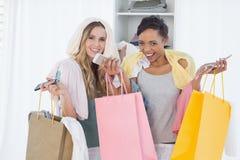 Жизнерадостные женщины стоя с хозяйственными сумками дома Стоковое фото RF