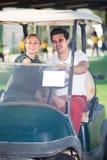 Жизнерадостные игроки в гольф человека и женщины ехать тележка гольфа Стоковая Фотография RF
