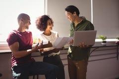 Жизнерадостные коллеги дела работая совместно окном на офисе Стоковое Фото