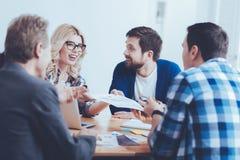 Жизнерадостные коллеги обсуждая новый контракт Стоковые Фото