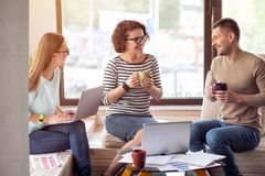 Жизнерадостные коллеги сидя в офисе Стоковые Изображения