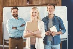 Жизнерадостные коллеги сотрудничая пока работающ в офисе Стоковое Изображение RF