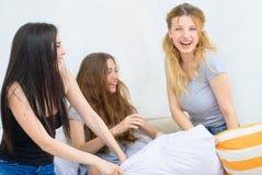 Жизнерадостные красивые подруги воюя на подушках Активные развлечения Стоковые Фотографии RF