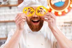 Жизнерадостные куски болгарского перца желтого цвета удерживания перед глазами Стоковое Изображение