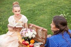 Жизнерадостные маленькие девочки делают пикник в парке Стоковые Фото