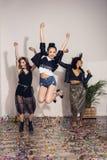 Жизнерадостные многонациональные девушки скача на партию внутри помещения Стоковые Фото