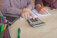 Жизнерадостные молодые бизнесмены сидя на таблице с компьтер-книжкой и протягивая в офисе Стоковое Изображение