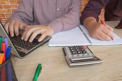 Жизнерадостные молодые бизнесмены сидя на таблице с компьтер-книжкой и протягивая в офисе Стоковые Изображения RF
