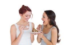 Жизнерадостные молодые женские друзья есть печенье совместно Стоковое Фото