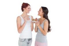 Жизнерадостные молодые женские друзья есть печенье совместно Стоковое фото RF