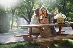 Жизнерадостные молодые женщины outdoors в вине парка выпивая делают selfie Стоковое Изображение RF