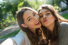 Жизнерадостные молодые женщины outdoors в вине парка выпивая делают selfie Стоковые Изображения