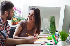 Жизнерадостные молодые дизайнеры работают в офисе Стоковая Фотография
