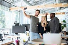 Жизнерадостные молодые коллеги в офисе coworking делают selfie Стоковая Фотография RF