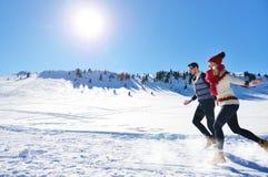 Жизнерадостные молодые пары имея потеху в парке зимы Стоковые Изображения RF