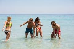 Жизнерадостные молодые пары наслаждаясь в море Стоковая Фотография