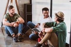 Жизнерадостные мужские коллеги говоря в офисе Стоковые Фотографии RF
