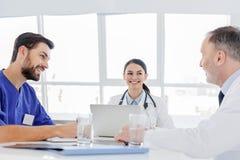Жизнерадостные доктора обсуждая здоровья человека с соответствием Стоковые Изображения RF