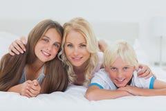 Жизнерадостные отпрыски и мать лежа на кровати стоковые фото