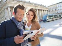 Жизнерадостные пары в городке смотря карту Стоковое фото RF