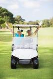 Жизнерадостные пары игрока в гольф сидя в багги гольфа Стоковое Изображение