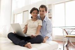 Жизнерадостные пары используя компьтер-книжку совместно дома Стоковые Изображения