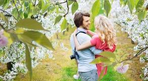 Жизнерадостные пары идя среди яблонь стоковое изображение