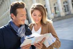 Жизнерадостные пары с картой в городе Стоковое Фото