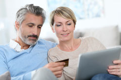 Жизнерадостные покупки пар на интернете стоковое фото