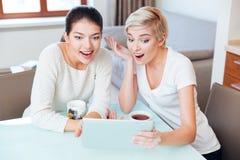 Жизнерадостные подруги используя планшет Стоковое фото RF