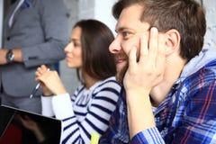 Жизнерадостные предприниматели на деловой встрече, семинаре, конференции или тренировке Стоковые Фотографии RF