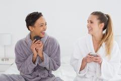Жизнерадостные друзья в обмене текстовыми сообщениями купальных халатов на кровати Стоковые Изображения