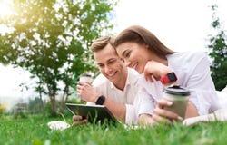 Жизнерадостные друзья отдыхая на траве Стоковые Фото