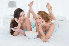 Жизнерадостные друзья с дистанционным управлением и попкорном в кровати Стоковая Фотография