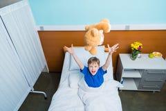 Жизнерадостные руки повышения мальчика и бросая плюшевый медвежонок в больничной койке Стоковые Фотографии RF