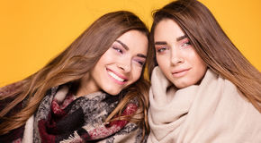 Жизнерадостные сестры близнецов представляя с шарфом Стоковые Фотографии RF
