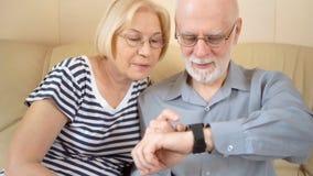 Жизнерадостные симпатичные старшие пары сидя на софе дома Используя smartwatch, просматривающ, читающ акции видеоматериалы
