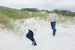 Жизнерадостные старшие пары бежать на пляже Стоковое Фото