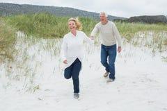Жизнерадостные старшие пары бежать на пляже Стоковая Фотография