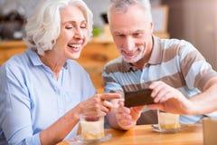 Жизнерадостные старшие пары сидя в кафе стоковая фотография