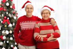 Жизнерадостные старшие пары с шляпами Санты перед рождеством t Стоковая Фотография