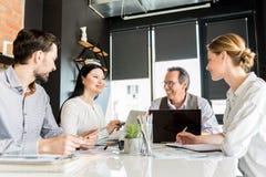 Жизнерадостные счастливые работники работая совместно в офисе Стоковое Изображение RF