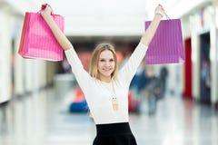 Жизнерадостные танцы девочка-подростка с хозяйственными сумками Стоковая Фотография