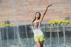 Жизнерадостные танцы девушки под двигателями воды в фонтане города Стоковое Изображение RF