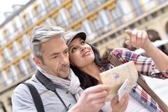 Жизнерадостные туристы читая карту Стоковые Изображения