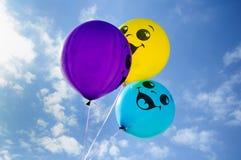 Жизнерадостные усмехаясь воздушные шары на фоне голубого неба Стоковое Изображение