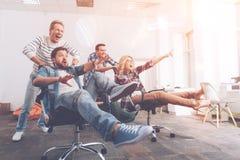 Жизнерадостные усмехаясь коллеги имея остатки в офисе Стоковое фото RF