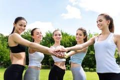 Жизнерадостные sporty девушки держа руки совместно Стоковые Фотографии RF