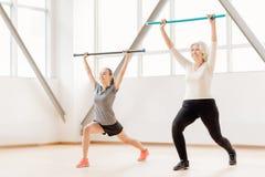 Жизнерадостные sporty женщины разрабатывая с гимнастическими ручками Стоковое Фото